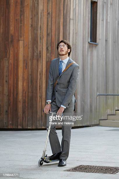 Businessman riding scooter in courtyard