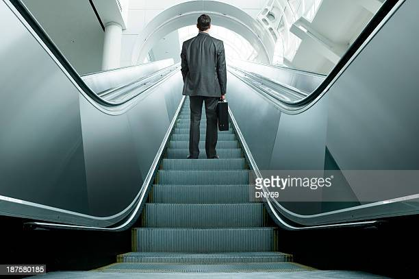 Businessman riding up an escalator