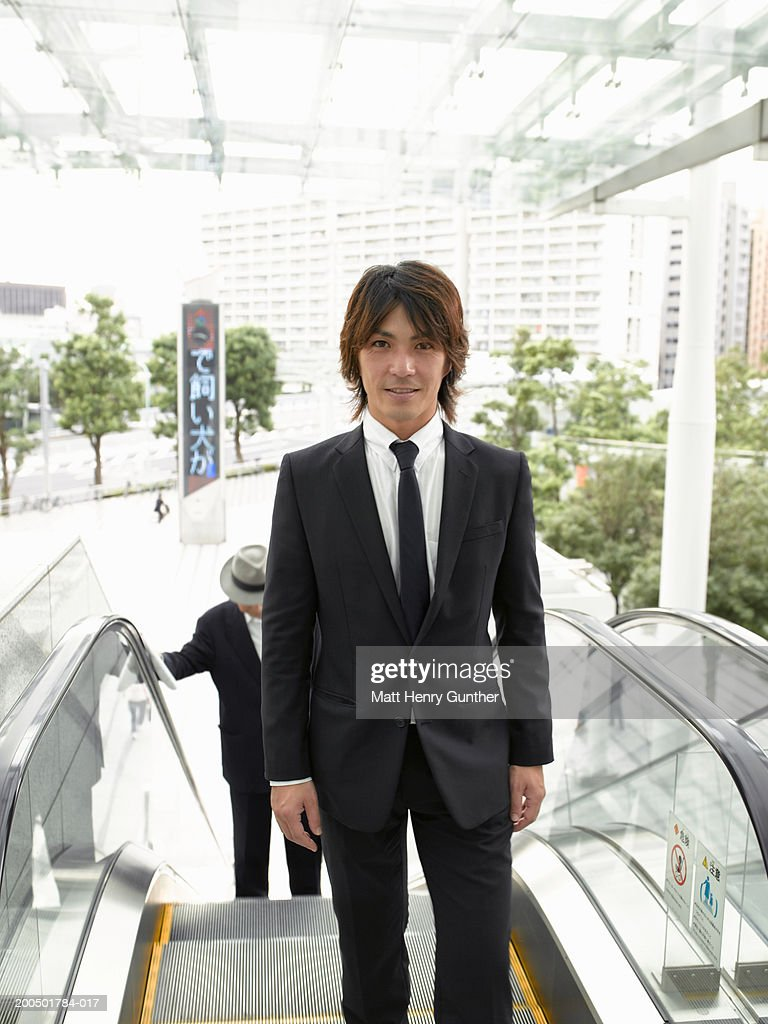 Businessman riding up escalator, smiling, portrait : Stock Photo
