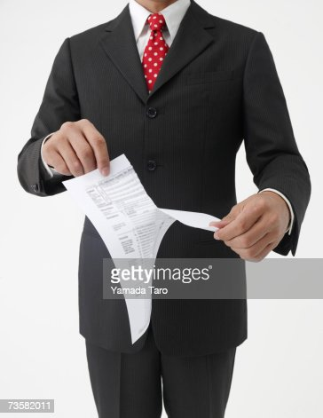 Businessman ripping paper, mid section