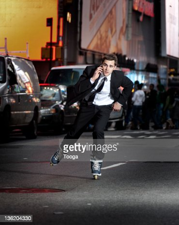 Businessman rollerblading and talking on phone
