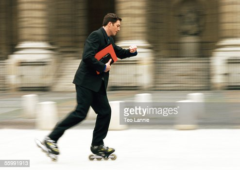 Businessman rollerblading in front of building and checking time, blurred.