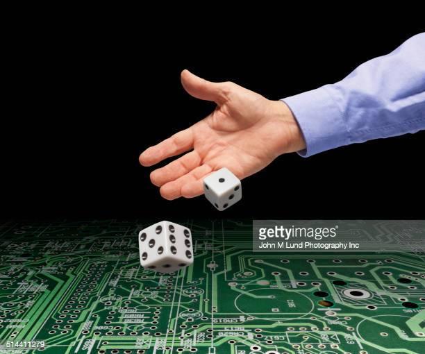 Businessman rolling dice on microchip