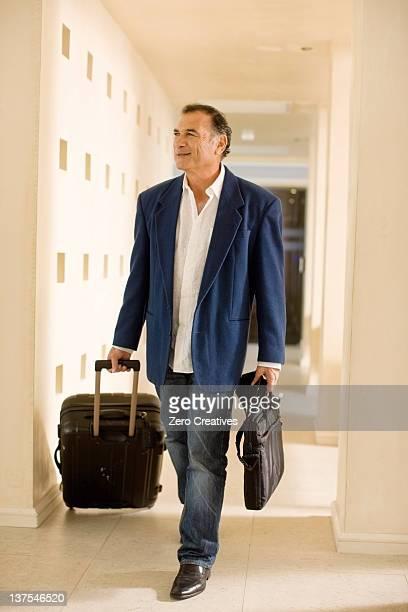 Homme d'affaires rouler vos bagages dans une passerelle