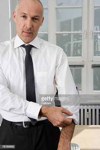 A businessman rolling up his sleeve