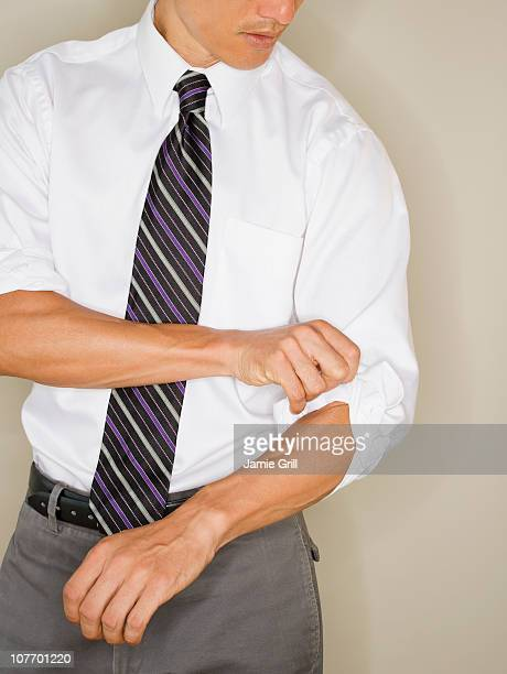 Businessman rolling up sleeves