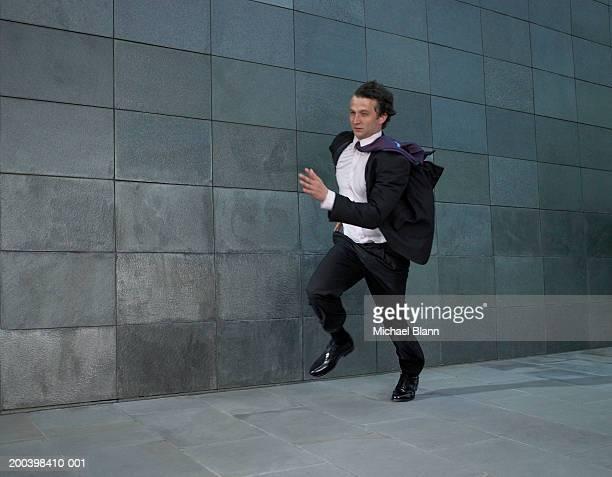 Businessman running against wind