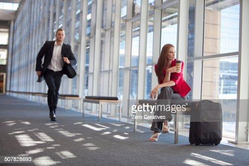 Businessman running along conference centre corridor