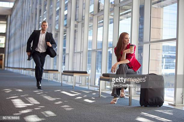 Businessman running along conference centre corridor