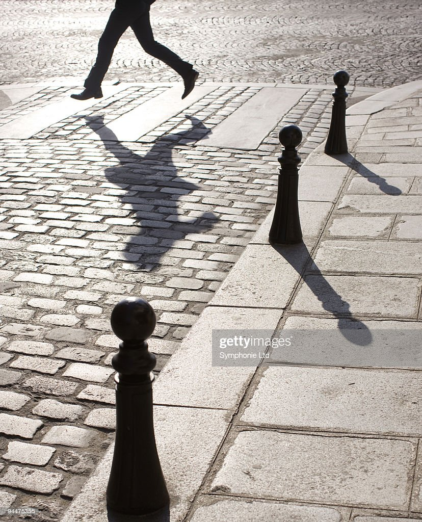 Businessman running along crosswalk on cobblestone street : Stock Photo