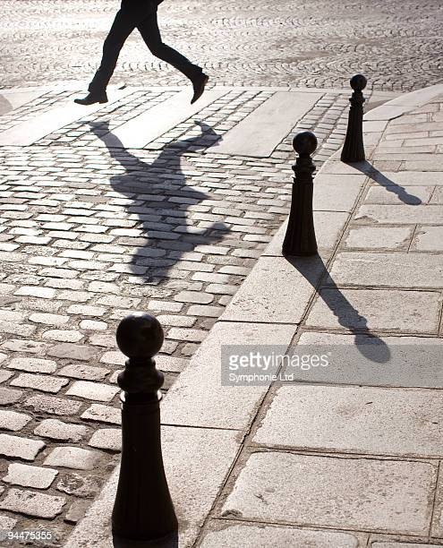 Businessman running along crosswalk on cobblestone street