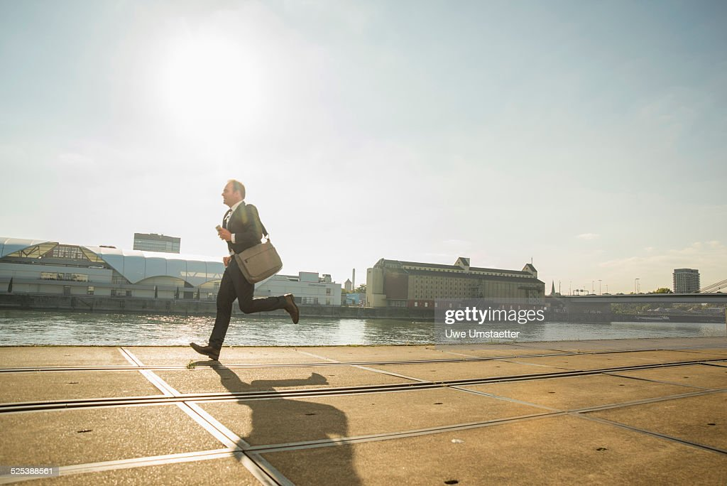 Businessman running along waterfront