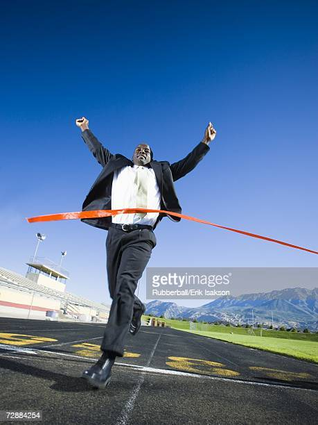 Businessman running and crossing finish line