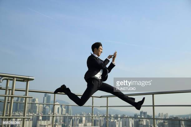 Businessman running and jumping, with cell phone