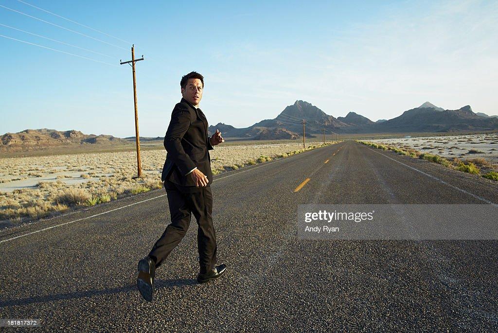 Businessman running down desert road, looking back : Stock Photo
