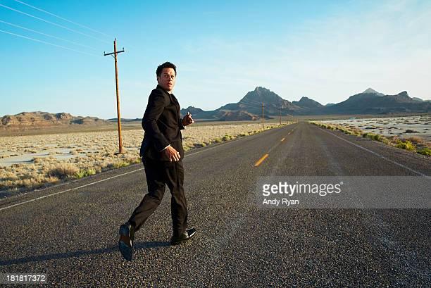 Businessman running down desert road, looking back