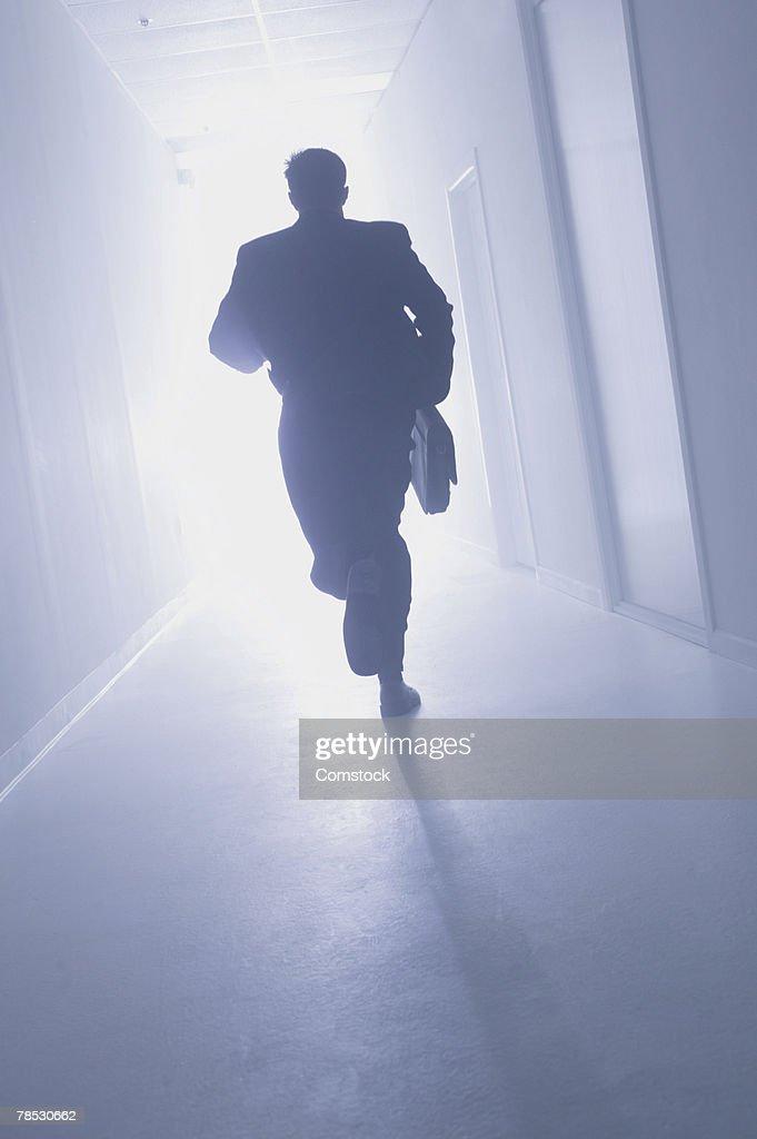 Businessman running down hallway toward light : Stock Photo