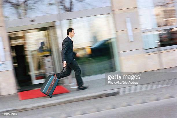 Businessman running down sidewalk, pulling suitcase behind him