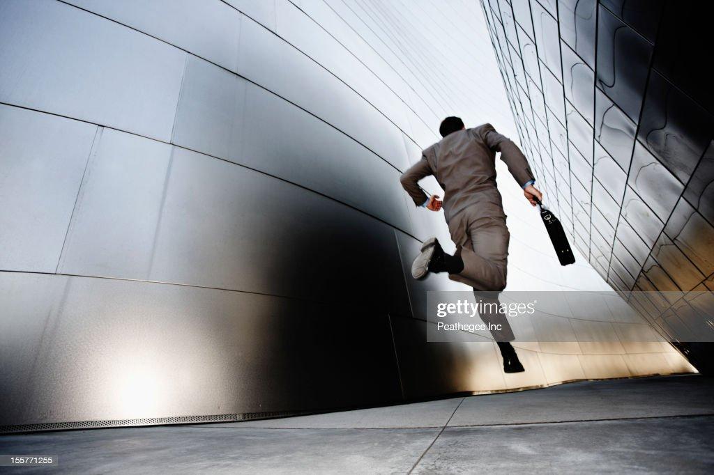 Businessman running down urban alley