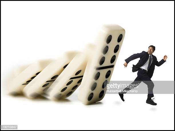 Businessman running from falling dominoes