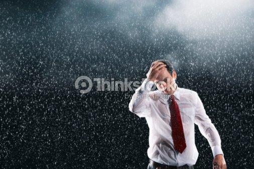 businessman running hands through wet hair standing in the rain