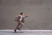 Businessman running in alley (motion blur)