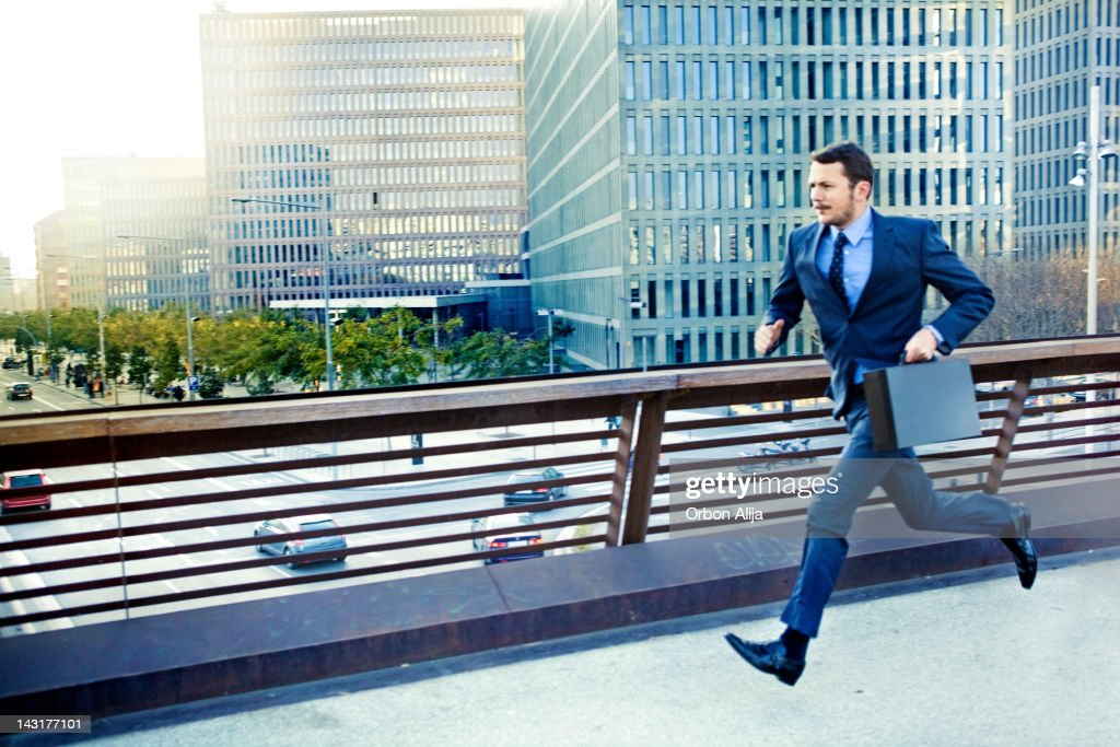 Businessman running in the city : Stock Photo