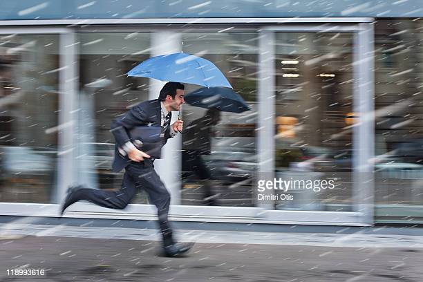 Businessman running in the rain with blue umbrella