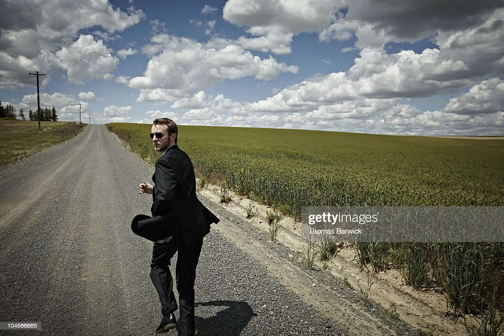 Businessman running looking over shoulder