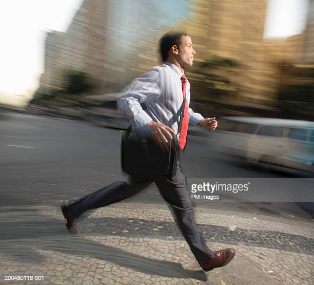 Businessman running on street, side view (blurred motion)