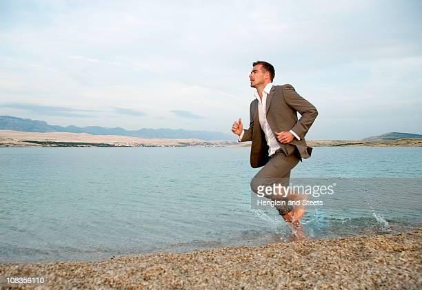 Businessman running on the beach