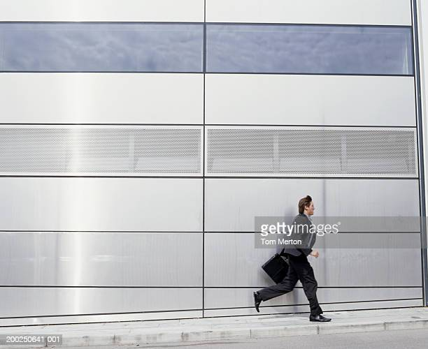 Businessman running past building carrying briefcase