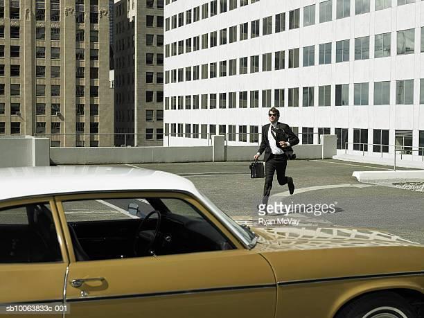 Businessman running toward car on parking lot