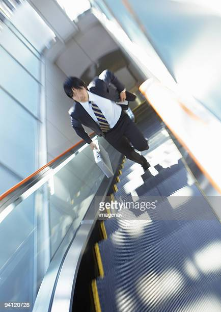 Businessman running up escalator