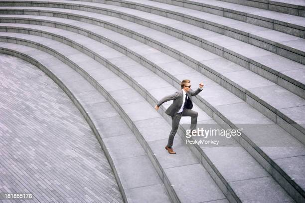 Businessman Running Up Massive Gray Staircase