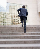 Businessman running up steps of office building