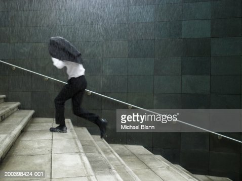 Businessman running up steps, sheltering under jacket, side view