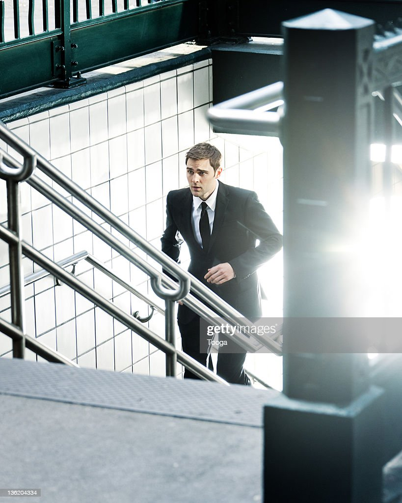 Businessman running up subway stairs : Stock Photo