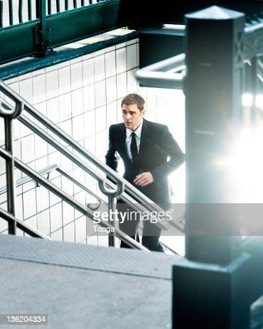 Businessman running up subway stairs : Stock Photo