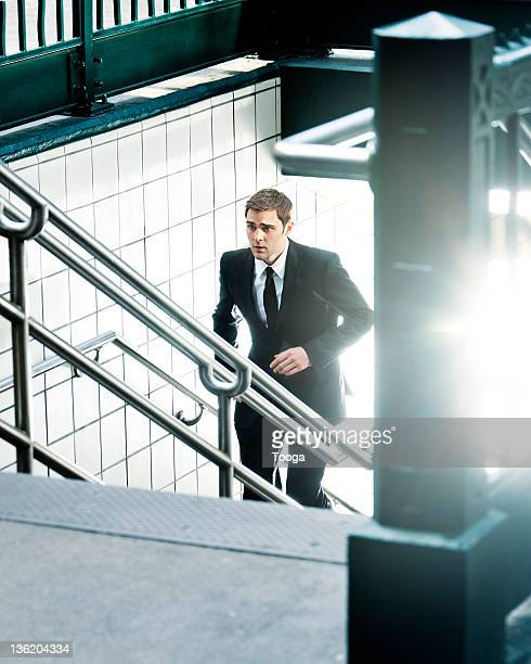 Businessman running up subway stairs