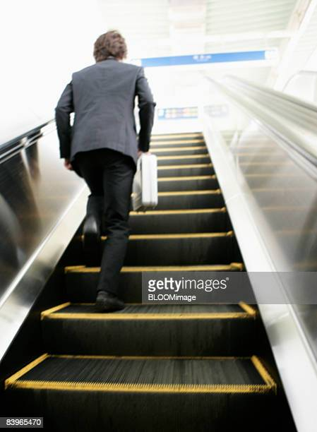 Businessman running up the escalator