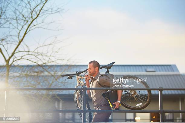 Businessman running with bicycle and folder in arms