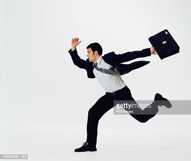 Businessman running with briefcase, side view