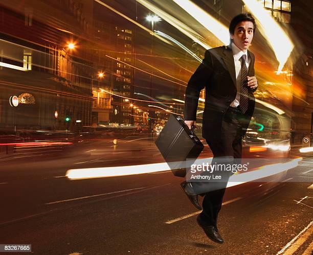 Businessman running with light streaking around him