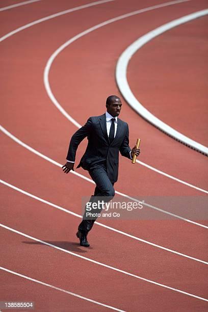 Businessman running with ralay baton