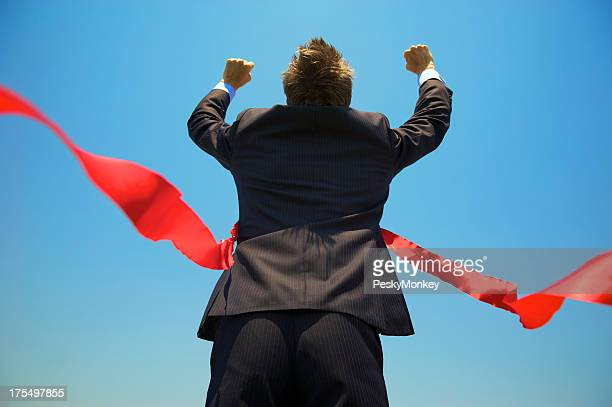 Businessman Runs Arms Up Through the Red Finish Line