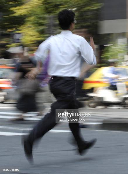 A businessman runs to cross a street in downtown Tokyo on August 27 2010 Japan's unemployment rate fell to 52 percent in July dropping by 01...
