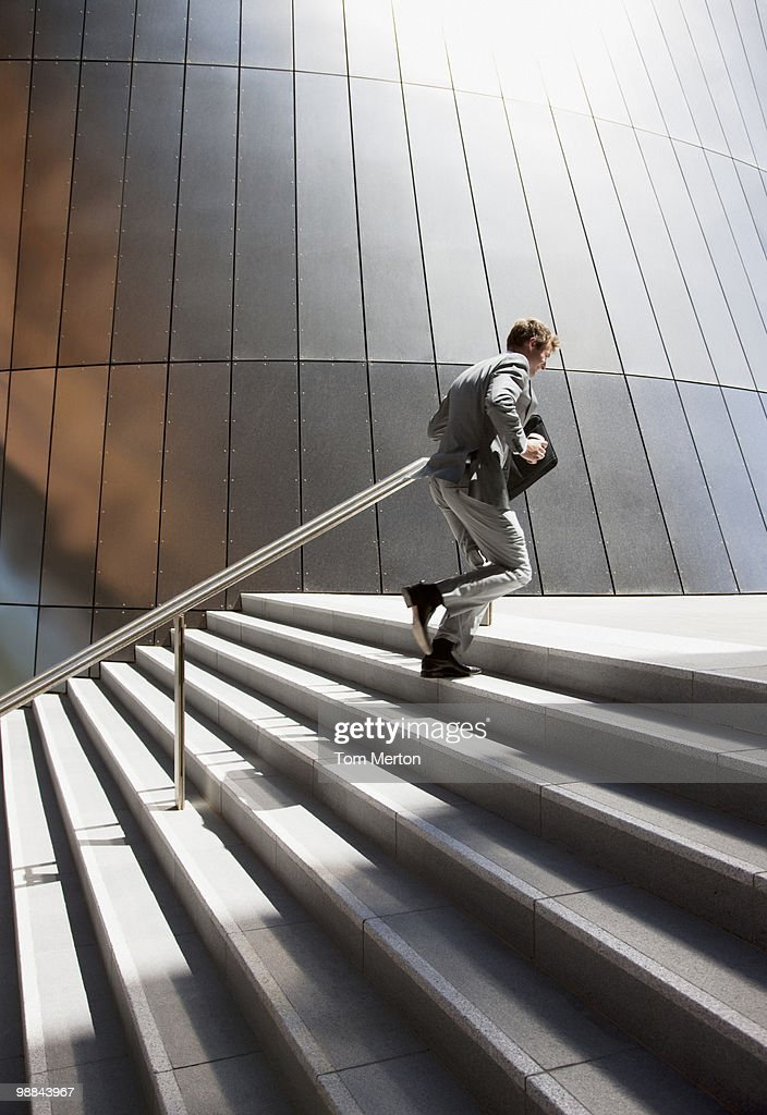 Businessman rushing up steps outdoors : Stock Photo