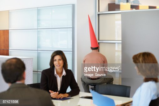 Businessman sat in corner with dunce cap