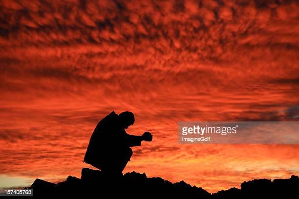 Uomo d'affari dicendo una preghiera al tramonto Silhouette